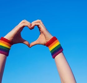 hands making a heart, with rainbow cuffs on